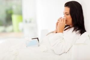 Erkaeltete Frau im Bett mit Schnupfen
