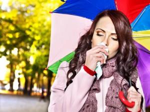 Frau mit Regenschirm und Taschentuch erkrankt an Erkältung