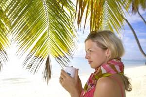Eine blonde Frau unter Palmen mit Erkältungstee