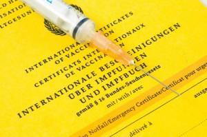 Gelber Impfpass mit offener Spritze darüber