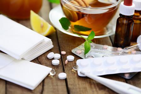 Tabletten und Erkältungstee auf einem Tisch