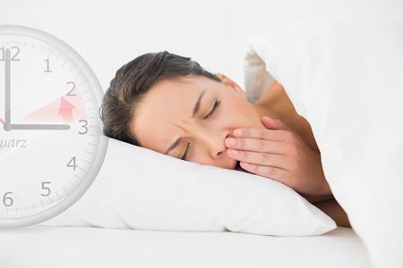 Eine verschlafene Mutter liegt gähnend im Bett