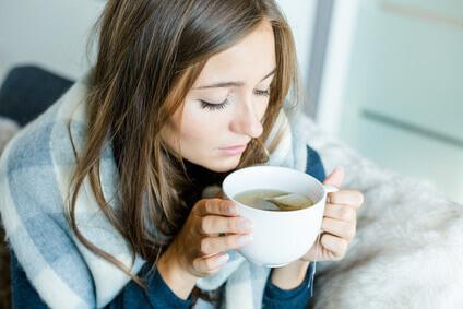 Frau mit Tee auf der Couch. Welche Erkältungsmythen stimmen?